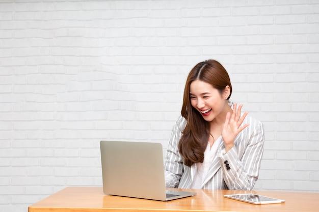Młoda azjatycka kobieta mówi patrzejący laptop i ono uśmiecha się podczas gdy pracujący w domu, wideokonferencja lub szkolenia online pojęciem.