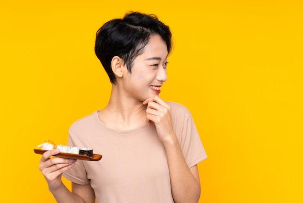 Młoda azjatycka kobieta myśleć pomysł i patrzeje stronę z suszi