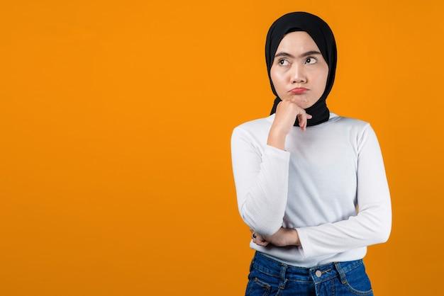 Młoda azjatycka kobieta myśli i wygląda na zdezorientowanego