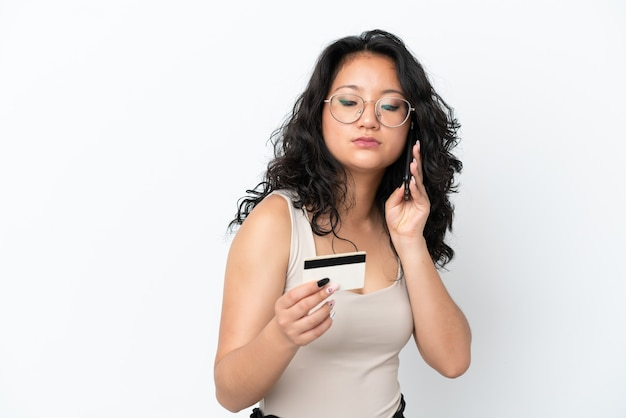 Młoda azjatycka kobieta na białym tle kupując za pomocą telefonu komórkowego za pomocą karty kredytowej