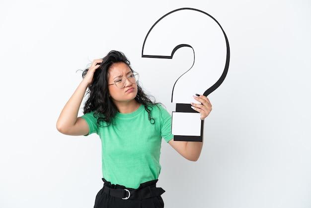 Młoda azjatycka kobieta na białym tle trzymająca ikonę znaku zapytania i mająca wątpliwości