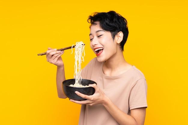 Młoda azjatycka kobieta nad odosobnioną kolor żółty ścianą trzyma puchar kluski z pałeczkami i je je