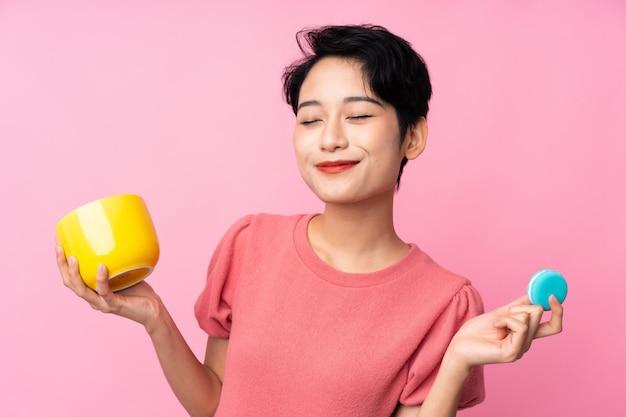Młoda azjatycka kobieta nad odosobnioną menchii ścianą trzyma kolorowych francuskich macarons i filiżankę mleka