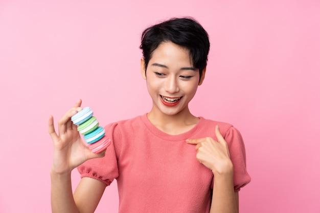 Młoda azjatycka kobieta nad odosobnioną menchii ścianą trzyma kolorowych francuskich macarons i świętuje zwycięstwo
