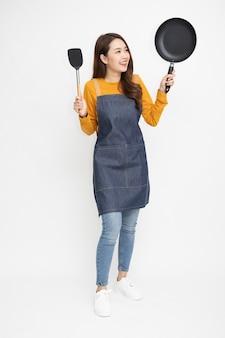 Młoda azjatycka kobieta nosząca fartuch kuchenny, gotująca i trzymająca patelnię na białym tle