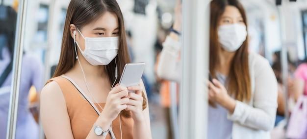 Młoda azjatycka kobieta pasażerka nosząca maskę chirurgiczną i słuchająca muzyki za pomocą inteligentnego telefonu komórkowego