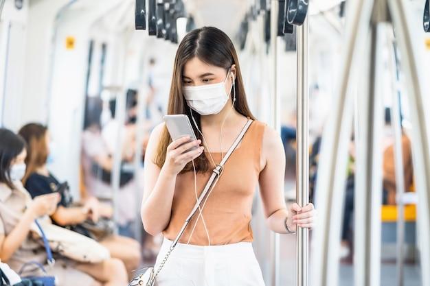 Młoda azjatycka kobieta pasażerka nosząca maskę chirurgiczną i słuchająca muzyki za pośrednictwem inteligentnego telefonu komórkowego