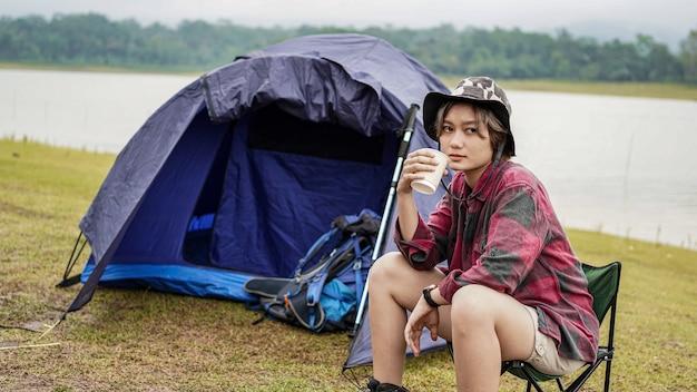 Młoda azjatycka kobieta pić kawę w fotelu
