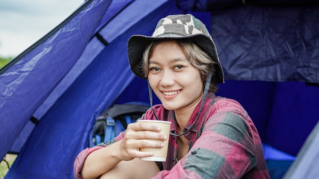 Młoda azjatycka kobieta pić kawę w namiocie kempingowym
