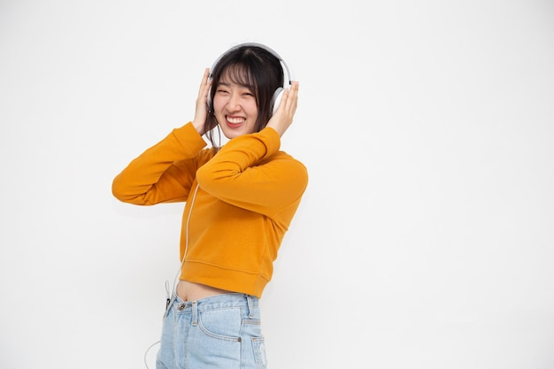 Młoda azjatycka kobieta piękna słuchająca muzyki ze słuchawkami w aplikacji do odtwarzania utworów na smartfonie na białym tle