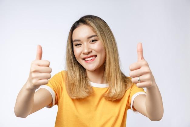 Młoda azjatycka kobieta pokazuje kciuki do góry