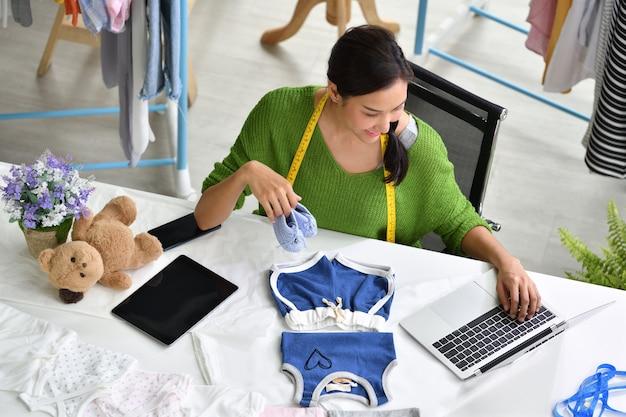 Młoda azjatycka kobieta przedsiębiorca / projektant mody dla dzieci ubrań pracuje w studiu