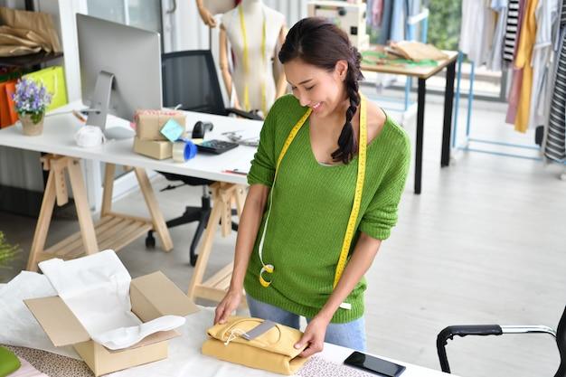 Młoda azjatycka kobieta przedsiębiorca / projektant mody pracuje w studiu, pakuje i wysyła produkt