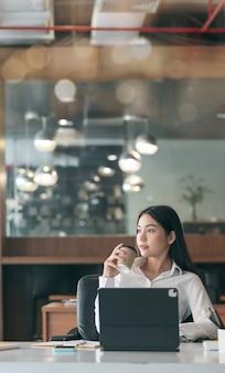 Młoda azjatycka kobieta relaks po pracy, trzymając filiżankę kawy i patrząc na zewnątrz.