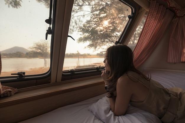 Młoda azjatycka kobieta relaksująca się i patrząca na widok w samochodzie kempingowym wieczorem na kempingu