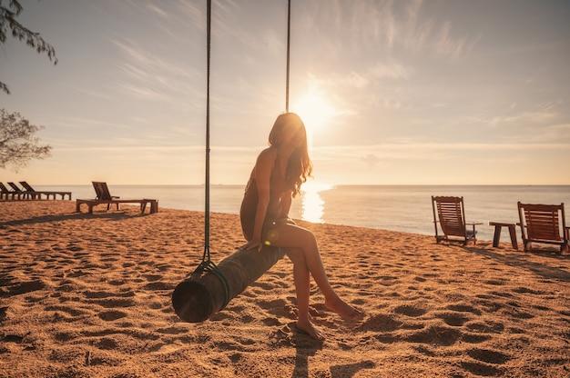 Młoda azjatycka kobieta relaksuje się na drewnianej huśtawce na plaży o wschodzie słońca nad tropikalnym morzem