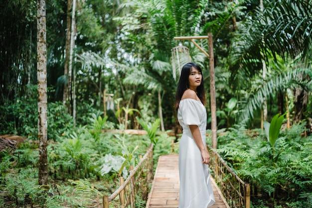Młoda azjatycka kobieta relaksuje w lesie, piękny żeński szczęśliwy używa relaksuje czas w naturze.