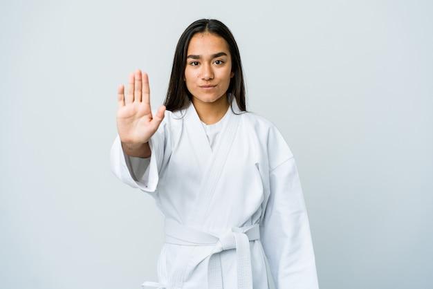 Młoda azjatycka kobieta robi karate na białym tle na białej ścianie stojącej z wyciągniętą ręką pokazując znak stopu, uniemożliwiając ci.
