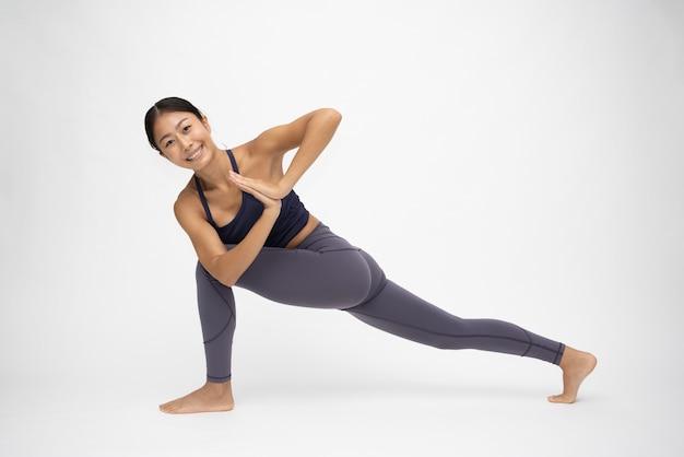 Młoda azjatycka kobieta robi praktyki jogi na białym tle, koncepcja jogi poza