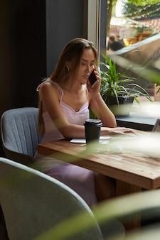 Młoda azjatycka kobieta siedzi w kawiarni z laptopem dzwoniąc przez smartfona