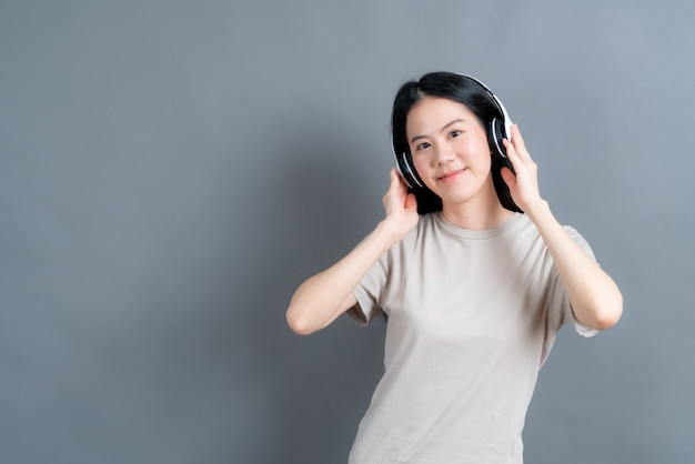 Młoda azjatycka kobieta słucha muzyki i słucha muzyki w słuchawkach
