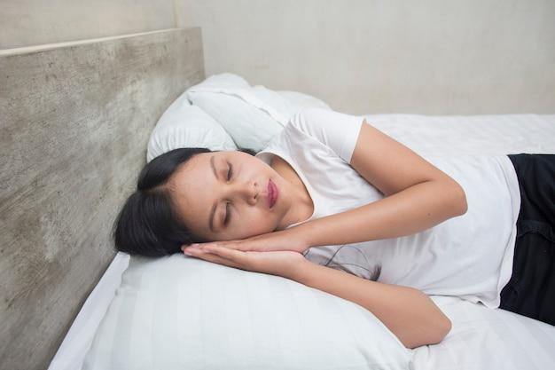 Młoda azjatycka kobieta śpi na łóżku