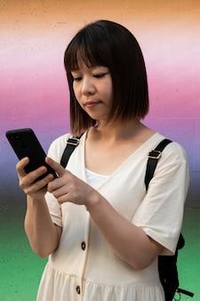 Młoda azjatycka kobieta sprawdzająca swój telefon na zewnątrz