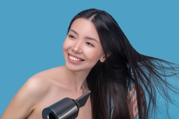 Młoda azjatycka kobieta suszy włosy i cieszy się