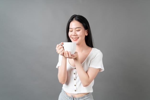Młoda azjatycka kobieta szczęśliwa twarz i ręka trzyma filiżankę kawy na szarej powierzchni