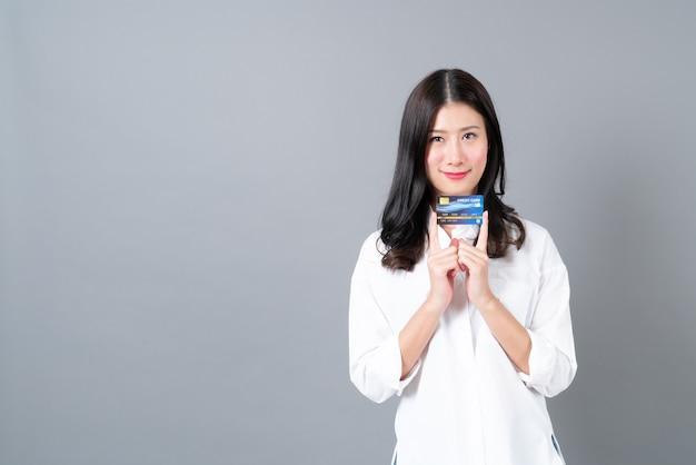 Młoda azjatycka kobieta szczęśliwa uśmiechnięta obecna karta kredytowa w ręku na szarym tle