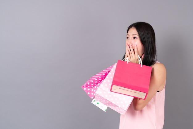 Młoda azjatycka kobieta szczęśliwa uśmiechnięta torba na zakupy w różowej sukience