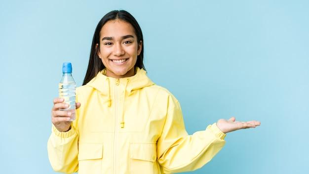 Młoda azjatycka kobieta trzyma butelkę wody na białym tle na niebieskiej ścianie, pokazując miejsce na kopię na dłoni i trzymając drugą rękę na talii.