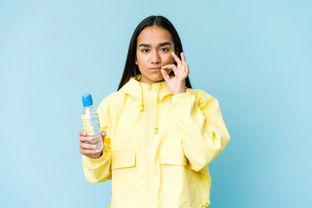 Młoda azjatycka kobieta trzyma butelkę wody na białym tle na niebieskiej ścianie z palcami na ustach, zachowując tajemnicę