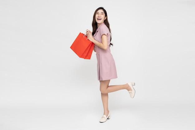 Młoda azjatycka kobieta trzyma czerwone torby na zakupy na białym tle