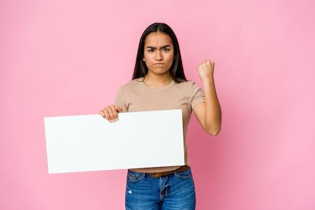 Młoda azjatycka kobieta trzyma czysty papier do białego czegoś na izolowanej ścianie pokazując pięść, agresywny wyraz twarzy.