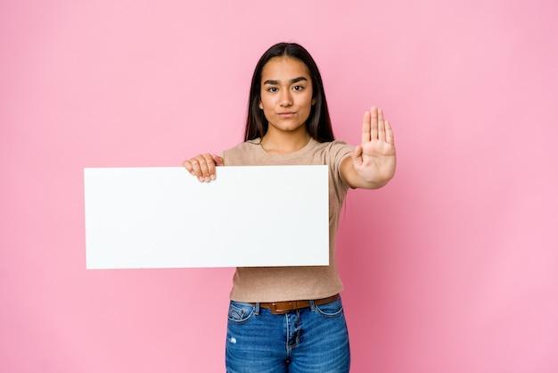 Młoda azjatycka kobieta trzyma czysty papier do białego czegoś stojącego z wyciągniętą ręką pokazując znak stopu, uniemożliwiając ci.