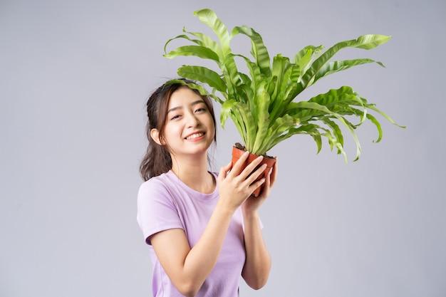 Młoda azjatycka kobieta trzyma garnki na szaro