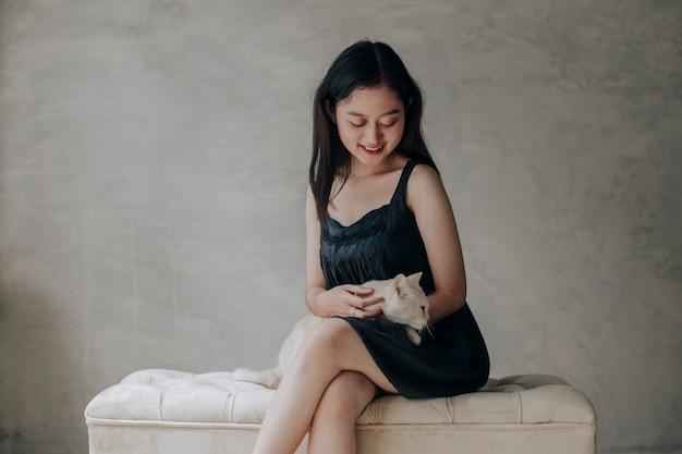 Młoda azjatycka kobieta trzyma i bawi się swoim ślicznym kotkiem kotem z pięknym momentem