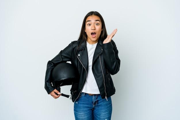Młoda azjatycka kobieta trzyma kask motocyklowy na białym tle zaskoczony i zszokowany.