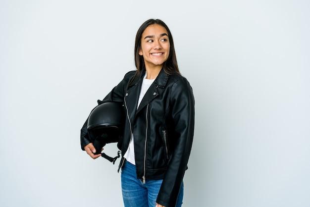 Młoda azjatycka kobieta trzyma kask motocyklowy na odizolowanej ścianie wygląda na bok uśmiechnięty, wesoły i przyjemny.