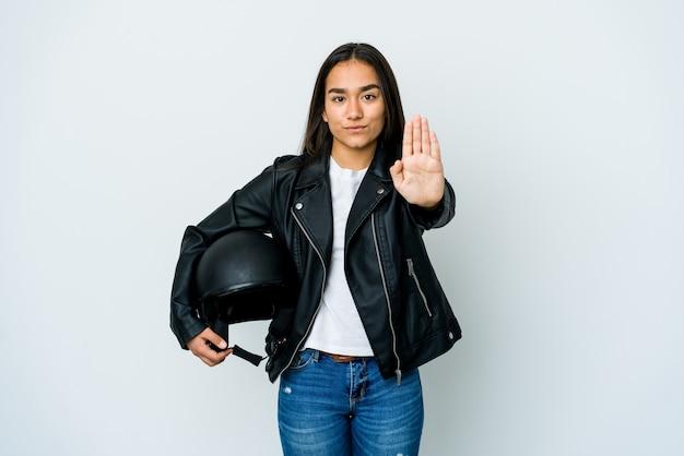 Młoda azjatycka kobieta trzyma kask motocyklowy, stojąc z wyciągniętą ręką pokazując znak stopu, uniemożliwiając ci.
