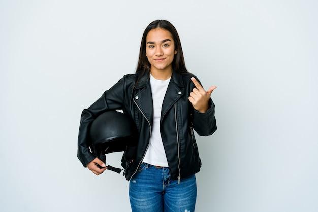 Młoda azjatycka kobieta trzyma kask motocyklowy, wskazując palcem na ciebie, jakby zapraszając, podejdź bliżej.