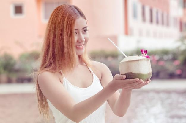 Młoda azjatycka kobieta trzyma kokosowego przygotowywającego jeść