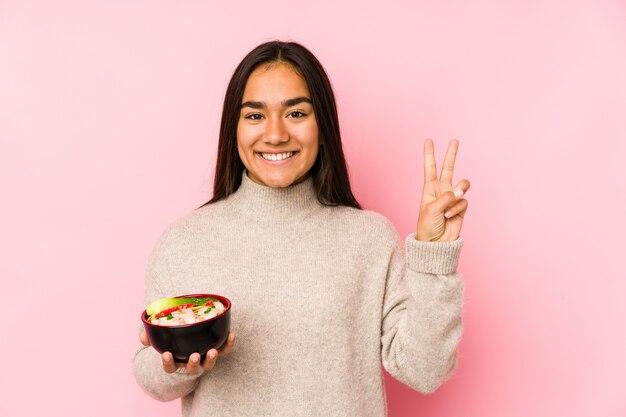 Młoda azjatycka kobieta trzyma miskę makaronu