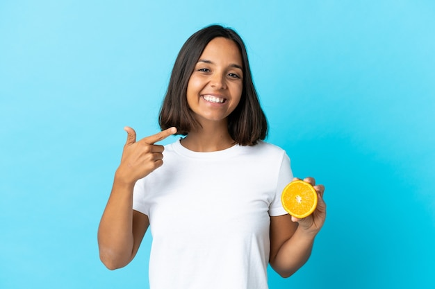Młoda azjatycka kobieta trzyma pomarańczowy na białym tle na niebiesko, dając kciuk w górę gestu