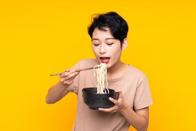 Młoda azjatycka kobieta trzyma puchar kluski z pałeczkami