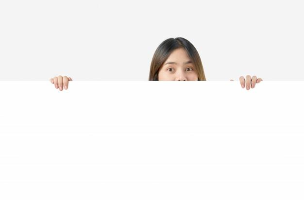 Młoda azjatycka kobieta trzyma pustego papier z uśmiechniętą twarzą i patrzeje na błękitnym tle