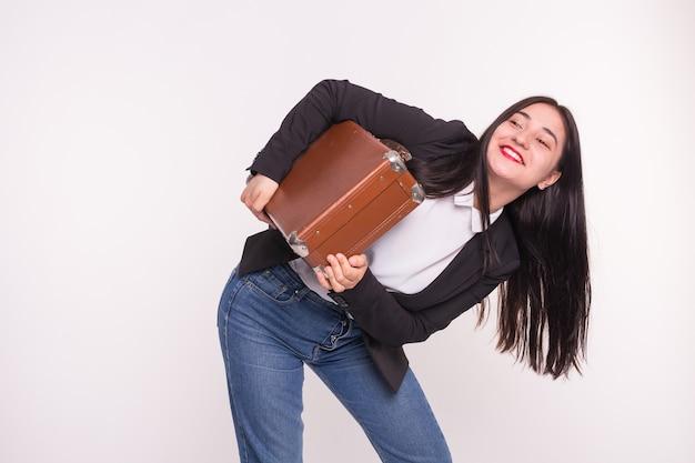 Młoda azjatycka kobieta trzyma skórzaną walizkę na białym tle.