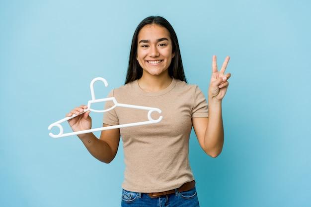Młoda azjatycka kobieta trzyma wieszak na białym tle na niebieskiej ścianie pokazuje numer dwa palcami