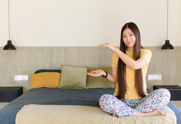 Młoda azjatycka kobieta trzymająca przedmiot obiema rękami po stronie kopii przestrzeni, pokazująca, oferująca lub reklamująca obiekt